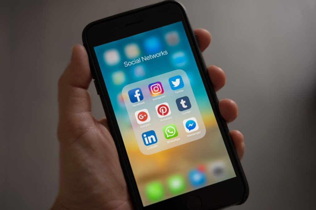 A hand with skin of white complexion holds a smart phone with social media icons visible on the screen.