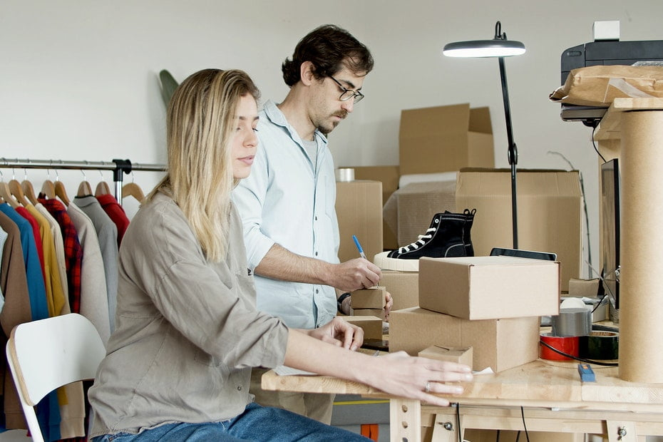Man and woman pack items in brown cardboard boxes.