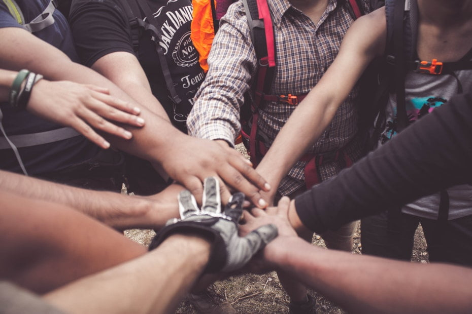 A group of people's arms reaching in to place their hands on top of each other in the form of a unity huddle.
