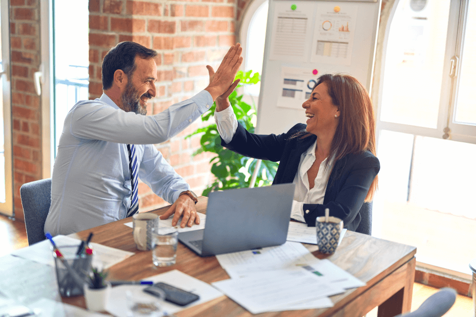 Stock photo of man and woman in business attire giving a high five.